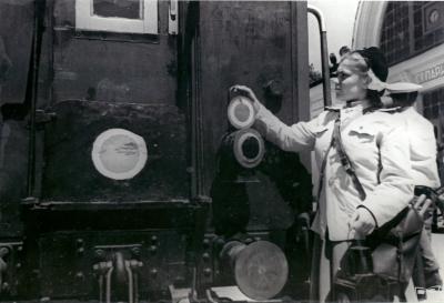 Главный кондуктор вешает фонарь на торец вагона